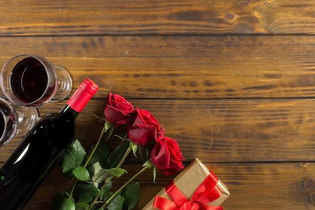 Decorazione romantica giorno di san valentino con rose, vino e scatola regalo su un tavolo in legno marrone