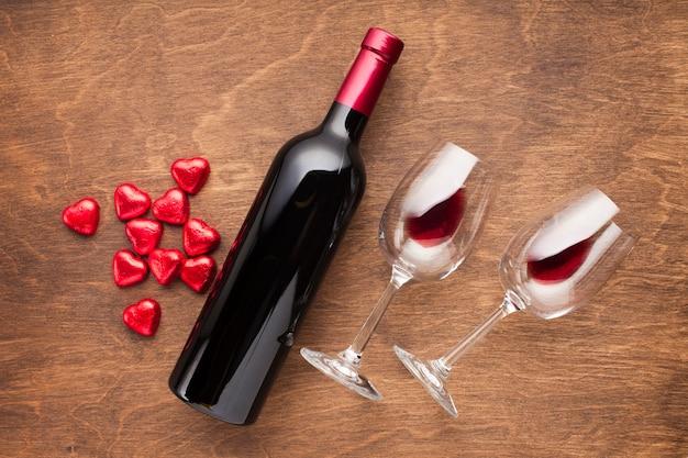 Decorazione vista dall'alto con caramelle a forma di cuore e vino