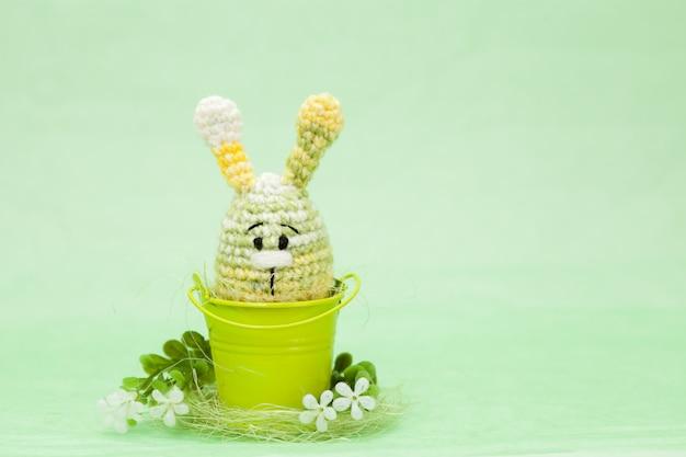 Decorazioni a maglia di uova di pasqua, fiori, coniglietto su uno sfondo verde, amigurumi