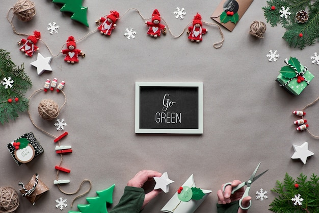 Decorazioni creative fatte a mano, cornice natalizia a zero sprechi. vista piana, vista dall'alto su carta artigianale. bigiotteria tessile, confezione regalo in carta decorata. natale ecologico. testo