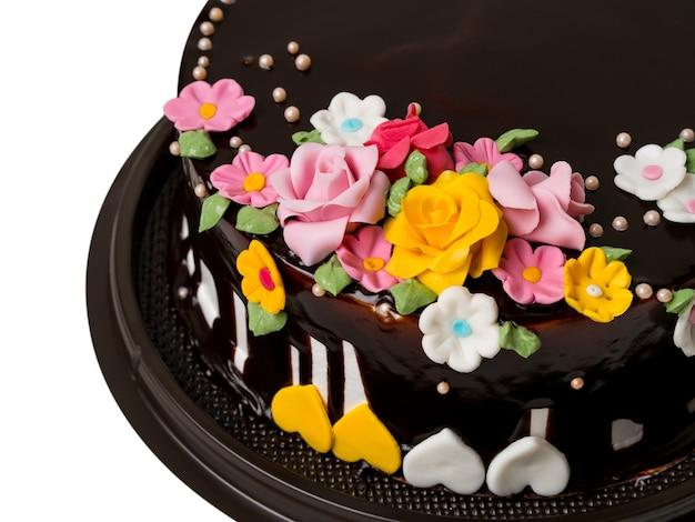 Decorazioni del dolce di cioccolato del primo piano con i frutti variopinti della glassa su fondo bianco