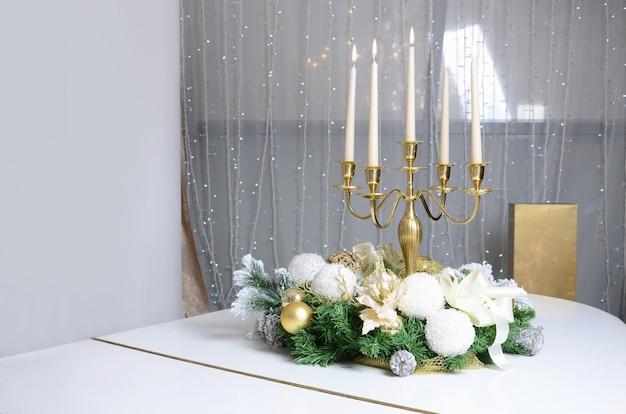 Decorazioni di capodanno e un candelabro d'oro con candele accese stanno sulla superficie di un pianoforte a coda bianco