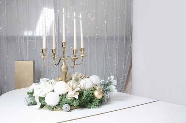 Decorazioni di capodanno e un candelabro d'oro con candele accese