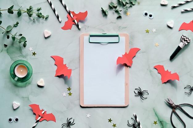 Decorazioni di halloween con ramoscelli di eucalipto, pipistrelli di carta rosso corallo, coriandoli, cuori di zucchero, rumori di festa, cannucce, occhi finti e ragni neri.
