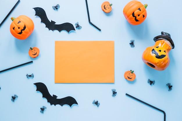 Decorazioni di halloween disposte attorno a un foglio di carta bianco