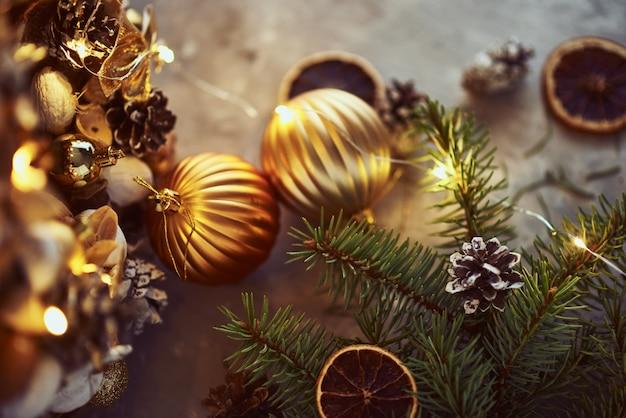 Decorazioni di natale con palline dorate, ramo di abete e luci ghirlanda su uno sfondo scuro