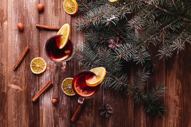 Decorazioni di natale e capodanno. due tazze di vin brulè con arance
