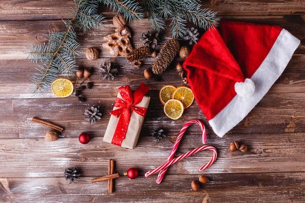 Decorazioni di natale e capodanno. la scatola attuale con il nastro rosso si trova su una tavola con i biscotti