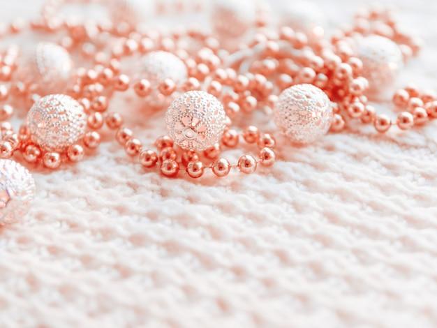 Decorazioni di natale e capodanno su bianco a maglia. lampadine in metallo con motivo delicato, perline rosso chiaro.