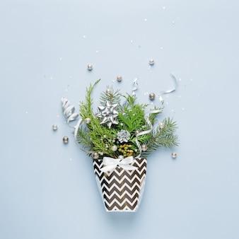 Decorazioni di natale e ramoscelli sempreverdi in un contenitore di regalo sullo spazio blu della copia.