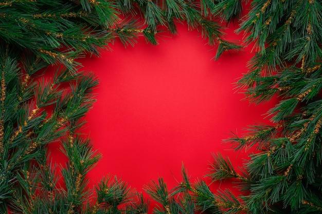 Decorazioni di natale o capodanno: rami di un albero di natale sul rosso con copyspace