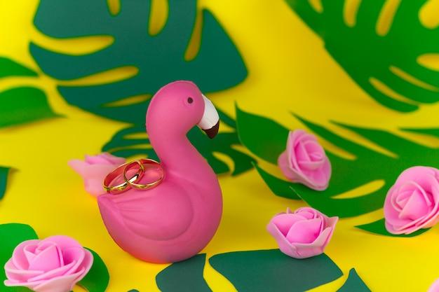 Decorazioni di nozze estive tropicali, anelli d'oro sul fenicottero
