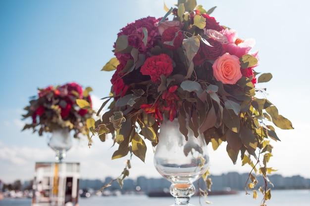 Decorazioni di nozze. registrazione del matrimonio all'aperto. mazzi di lusso con fiori rossi