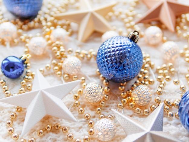 Decorazioni di stelle di natale e capodanno su bianco a maglia. lampadine in metallo con motivo delicato, perline dorate e palline blu.
