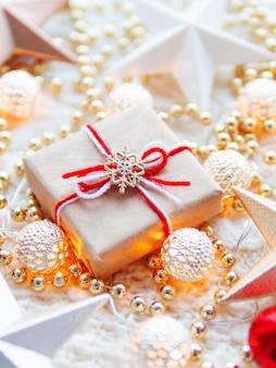 Decorazioni di stelle di natale e capodanno su bianco a maglia. scatola regalo avvolta in carta artigianale con simbolo fiocco di neve su di esso, lampadine in metallo con motivo delicato, perline dorate, palline rosse.
