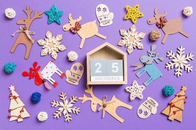 Decorazioni e giocattoli festivi. vista dall'alto del calendario in legno. il venticinque dicembre. concetto di buon natale
