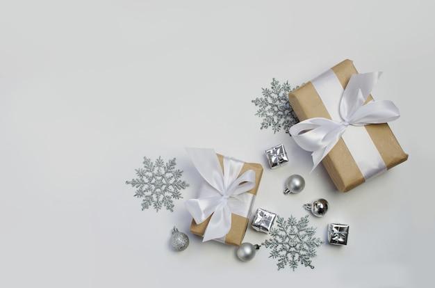 Decorazioni e presente d'argento su una priorità bassa bianca