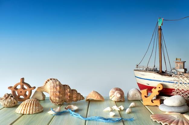 Decorazioni estive: conchiglie, nave di legno, ancora e lapidato su blu, spazio