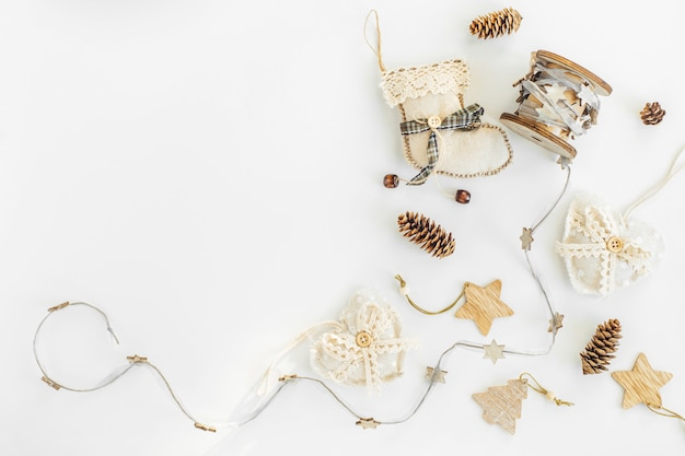 Decorazioni fatte a mano rustiche di natale da materiali naturali e ghirlanda su un bianco con copyspace.