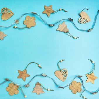 Decorazioni fatte a mano rustiche di natale da materiali naturali e ghirlanda su un blu con copyspace.