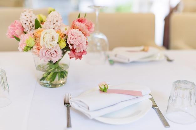 Decorazioni floreali da tavola per feste e cene nuziali. tavolo apparecchiato per il ricevimento di nozze nel ristorante all'aperto.