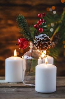 Decorazioni natalizie, candele accese, abete rosso su uno sfondo di legno. nuovi anni . cartolina