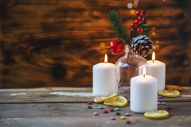 Decorazioni natalizie, candele accese, caramelle, agrumi, abete rosso su uno sfondo di legno. nuovi anni . cartolina
