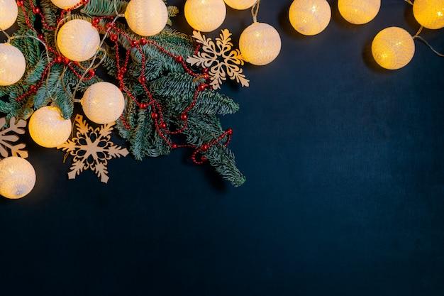 Decorazioni natalizie con abete, ghirlanda splendente e fiocchi di neve su sfondo nero con copyspace