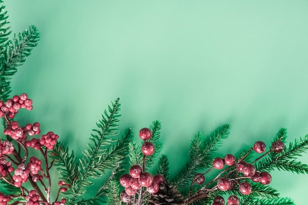 Decorazioni natalizie con bacche rosse e rami di abete su un bellissimo sfondo di menta.
