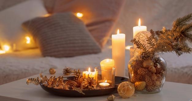 Decorazioni natalizie con candele accese sul tavolo bianco contro il divano con plaid e cuscini.