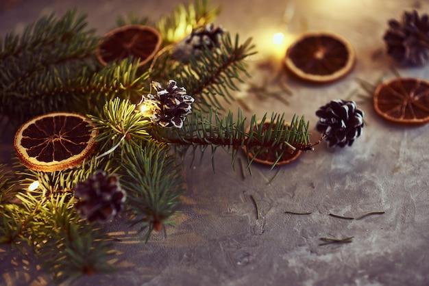 Decorazioni natalizie con ghirlanda di luci, pigne e ramo di abete su un buio