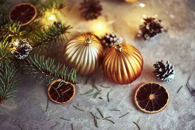 Decorazioni natalizie con palline dorate, ramo di abete e luci ghirlanda