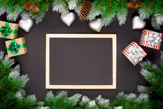 Decorazioni natalizie con rami di abete su uno sfondo scuro con spazio di copia