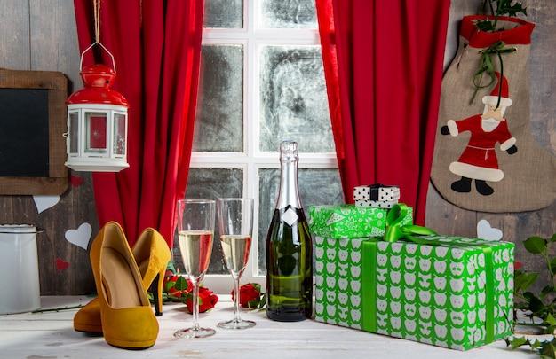 Decorazioni natalizie con regali, bicchieri e bottiglia di champagne