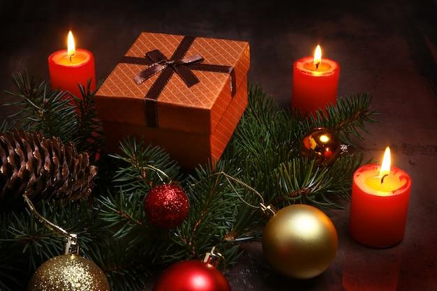 Decorazioni natalizie con scatole regalo, candele rosse, albero di natale e palline colorate. messa a fuoco selettiva.