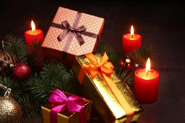 Decorazioni natalizie con scatole regalo, candele rosse, albero di natale e palline colorate.