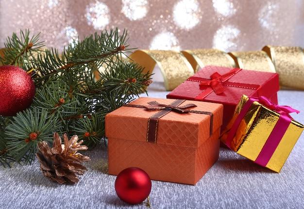 Decorazioni natalizie con scatole regalo, palline colorate di natale, albero di natale e coni su uno sfocato, scintillante e favoloso