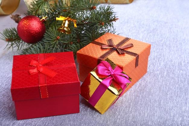 Decorazioni natalizie con scatole regalo, palline colorate di natale e albero di natale su un sfocato, scintillante e favoloso.