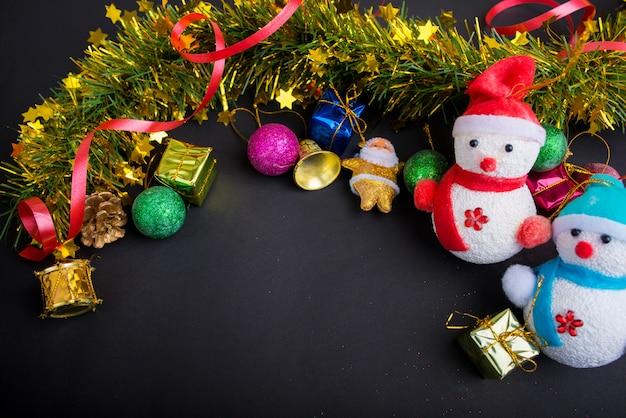Decorazioni natalizie con sfondo nero scuro. vista dall'alto, copia spazio. palla, confezione regalo, babbo natale, nastro, ramo di pino, campana, pupazzi di neve.