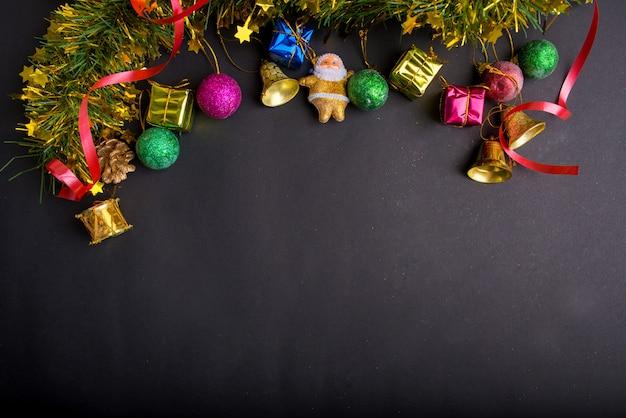 Decorazioni natalizie con sfondo nero scuro. vista dall'alto, copia spazio. palla, confezione regalo, babbo natale, nastro, ramo di pino, campana.
