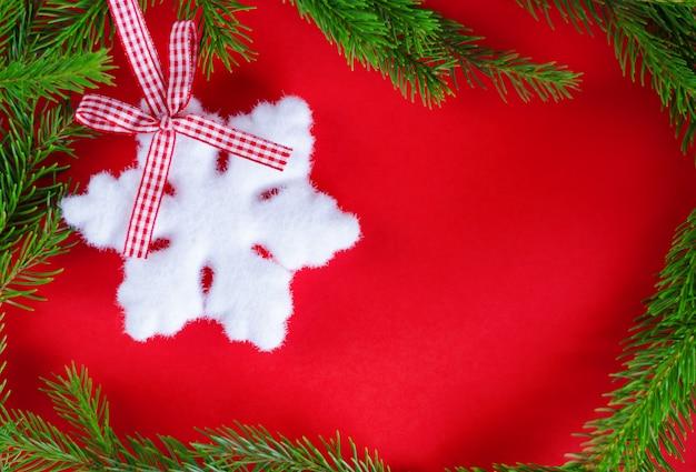 Decorazioni natalizie e auguri. fiocco di neve sul rosso. copyspace. vista dall'alto. composizione del telaio