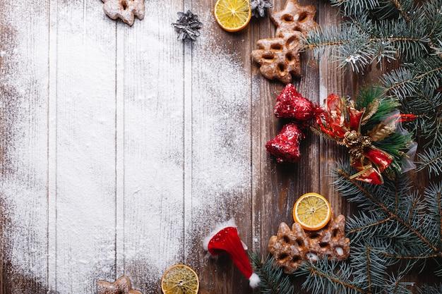 Decorazioni natalizie e luogo per il testo. la neve bianca si trova su un tavolo circondato con i biscotti