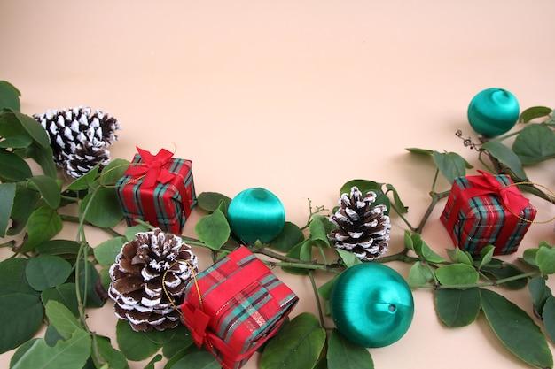 Decorazioni natalizie e viti e pigne secche su uno sfondo giallo chiaro.