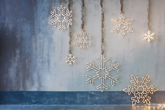 Decorazioni natalizie in legno per pareti. fiocchi di neve incandescente con ghirlanda di luci su sfondo grigio cemento. sfondo di natale, tema vacanze invernali.