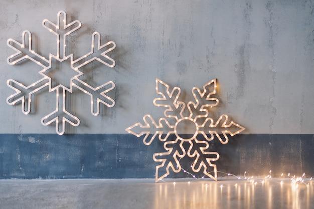 Decorazioni natalizie in legno per pareti. fiocchi di neve incandescente con ghirlanda di luci su sfondo grigio cemento.