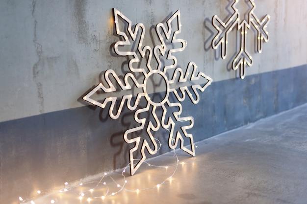 Decorazioni natalizie in legno per pareti. fiocchi di neve incandescente con ghirlanda di luci sul muro di cemento grigio