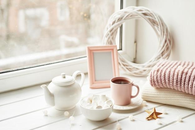 Decorazioni natalizie, palline, plaid di lana alla finestra, concetto di comfort domestico, feste invernali stagionali. . tazza di natale rosa con marshmallow.