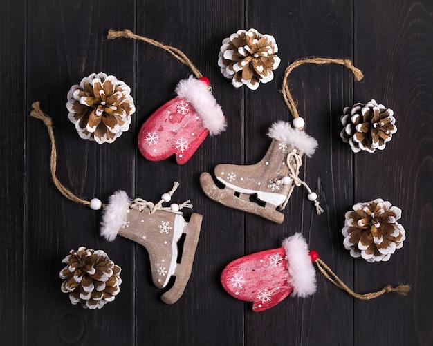 Decorazioni natalizie pattini, guanti, fiocchi di neve, coni su fondo in legno