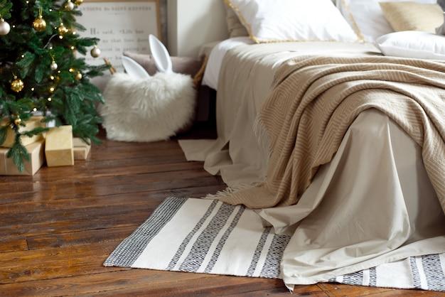 Decorazioni natalizie per appartamento, arredamento accogliente scandinavo, letto con calde coperte lavorate a maglia accanto all'albero di natale. luci e ghirlande.