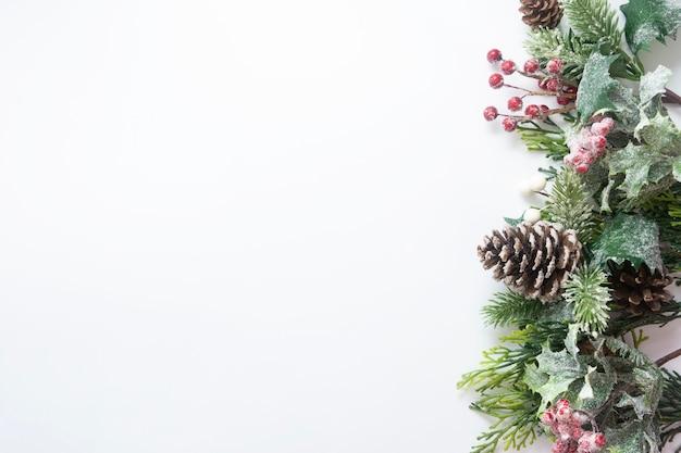 Decorazioni natalizie, rami di abete in stile, pigne su sfondo bianco.